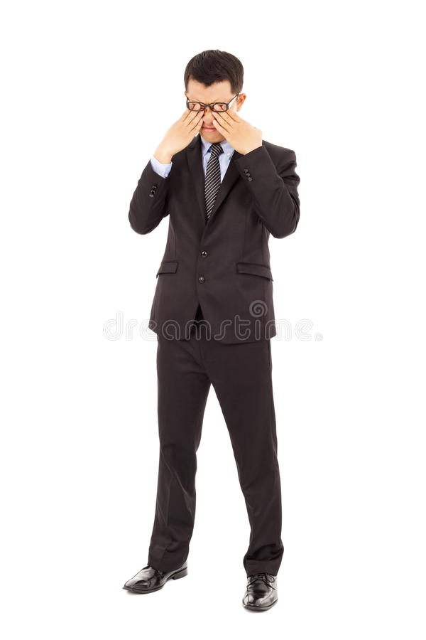 Tired young businessman rubbing his eyes stock images