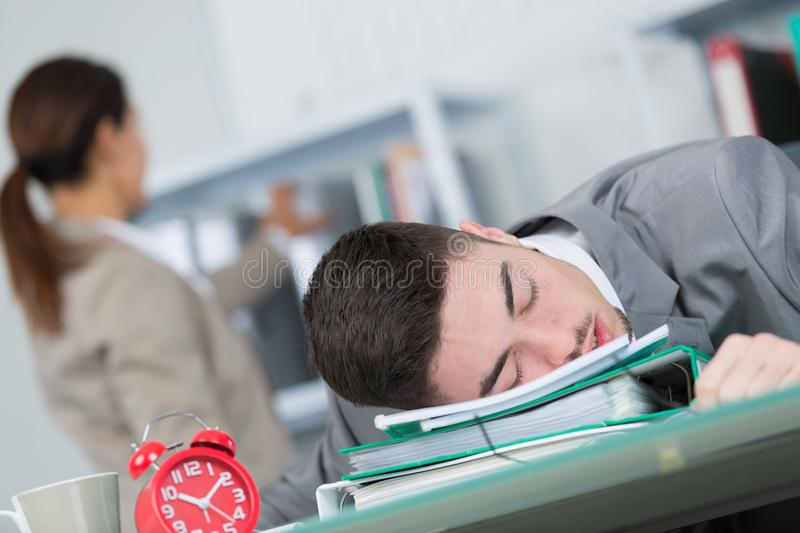 Tired young businessman sleeping in office royalty free stock photo