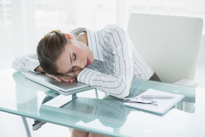 Tired young businesswoman sleeping in her office royalty free stock images
