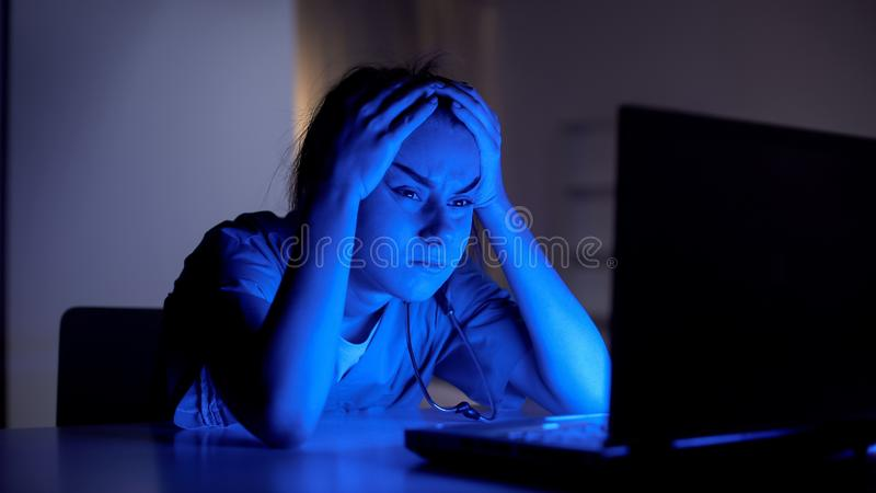 Tired young doctor working on computer at night, preparing for examination stock photo