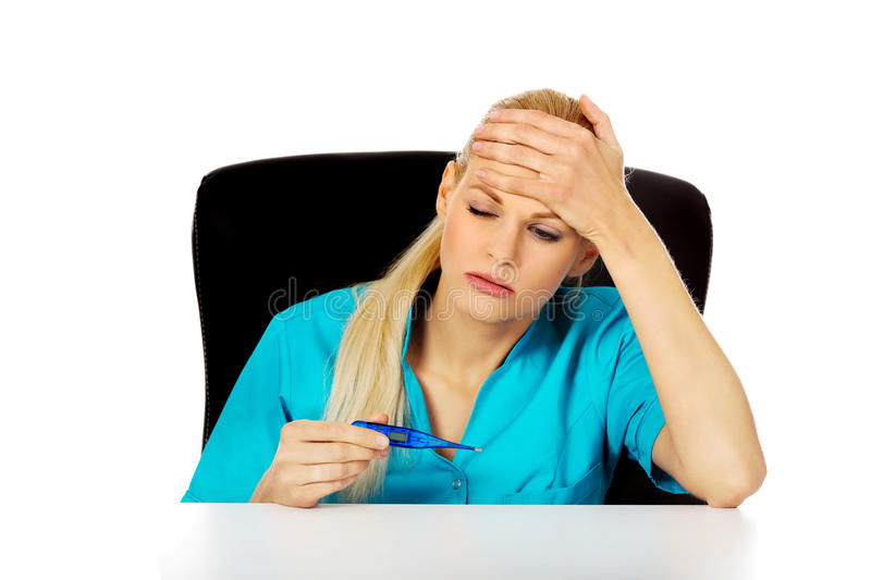 Tired young female doctor or nurse sitting behind the desk and holding termomether royalty free stock photography