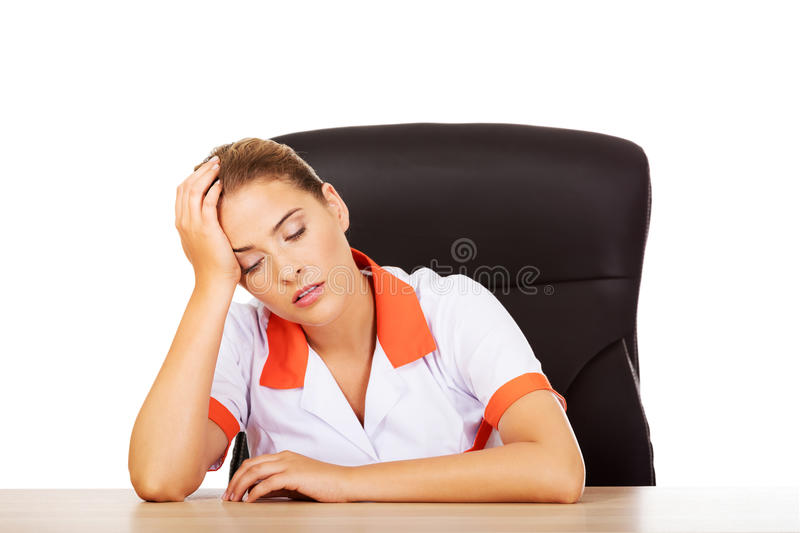 Tired young female doctoror nurse sitting behind the desk stock photo