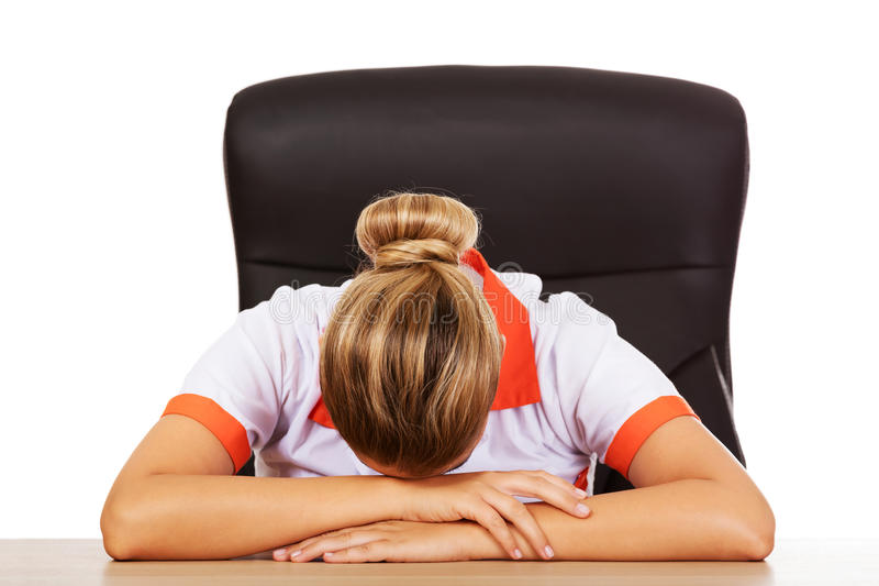 Tired young female doctoror nurse sleeping on the desk stock image
