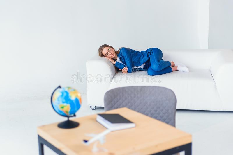 Tired young female student in casual clothing sleeps on white sofa. Beautiful woman resting after hard studying or. Tired young female student in casual clothing stock photography