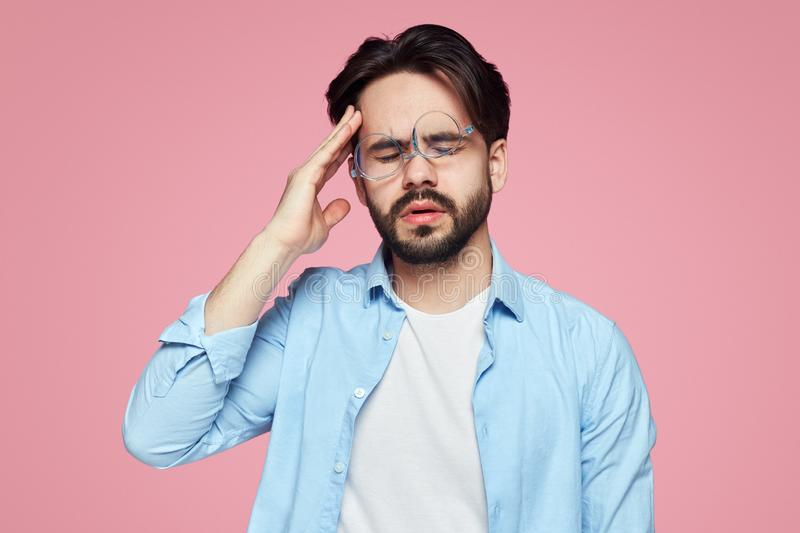 Tired young male has terrible headache after work, closes eyes and keeps hands on temples as feels pain over pink backdrop royalty free stock photo