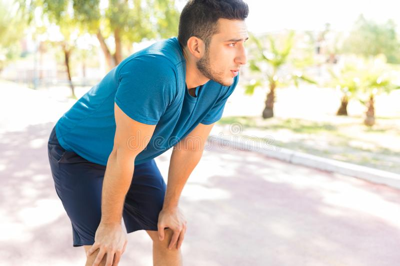 Tired Male Jogger With Hands On Knees In Park stock photography