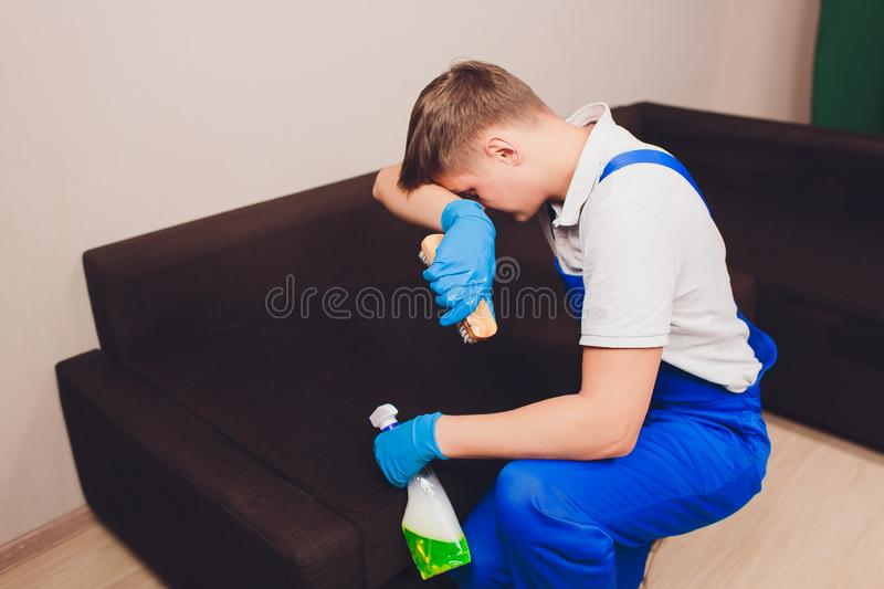 Tired young man sitting on sofa in living room. extractor, couch couch, chemistry, washing, cleaning. blue protective stock images
