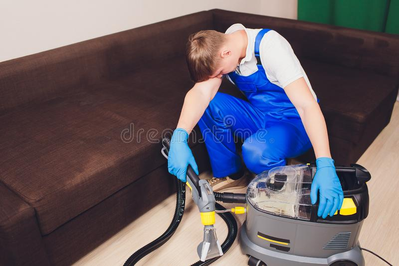 Tired young man sitting on sofa in living room. extractor, couch couch, chemistry, washing, cleaning. working blue royalty free stock image