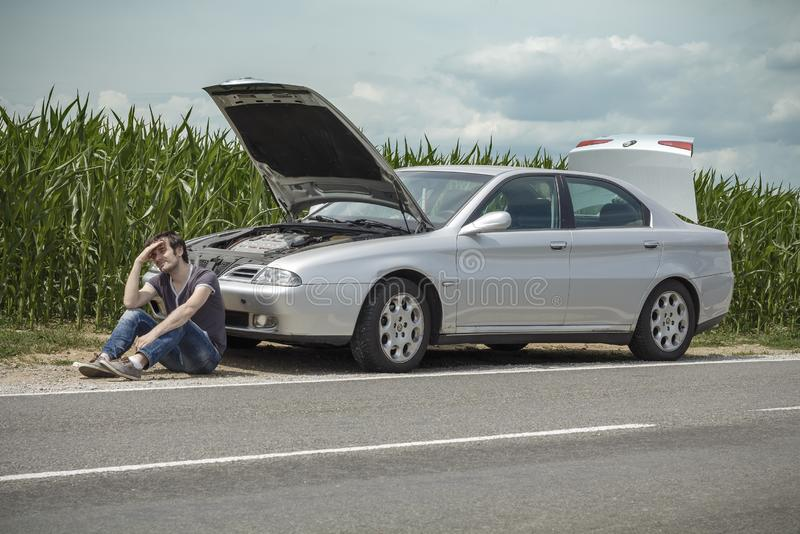 Tired young man waiting a help while sitting near the broken car at the side of empty road near corn field stock images