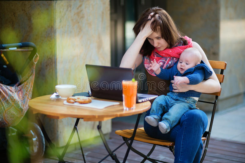Tired young mother working oh her laptop stock photos