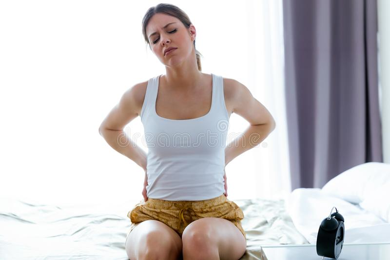 Tired young woman with back pain sitting on the bed at home. stock images