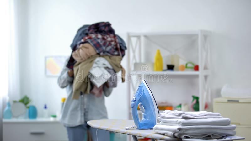 Tired young woman carrying pile of clothes to iron board, domestic routine stock images