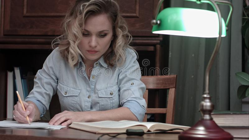 Tired young woman finishing her report, closing the book, turning the lamp off and leaving her desk stock photo