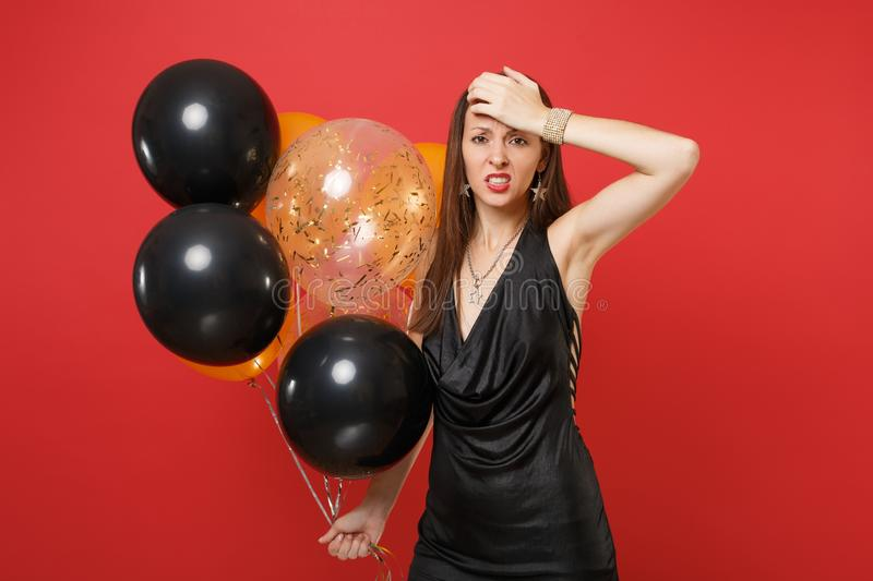 Tired young woman in little black dress suffering from headache putting hand on head holding air balloons celebrating. Isolated on red background. Happy New stock photos