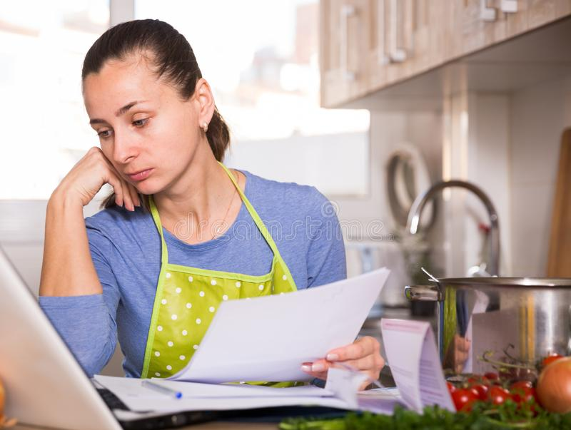 Young woman reading recipe in the kitchen. Tired young woman reading recipe in the kitchen royalty free stock photography