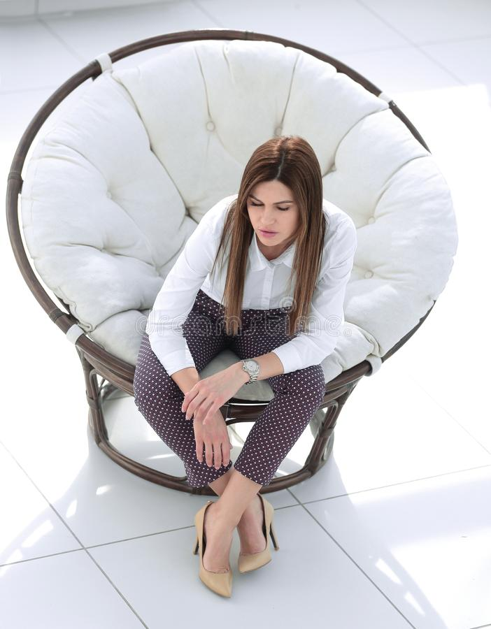 Tired young woman sitting in comfortable round chair royalty free stock photos