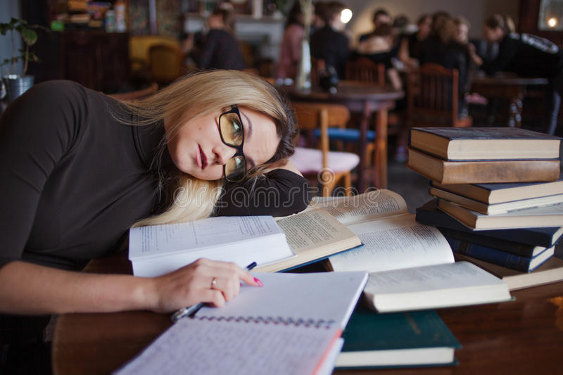 Tired young woman student of the University. Preparing exam and learning lessons in public library. royalty free stock photo