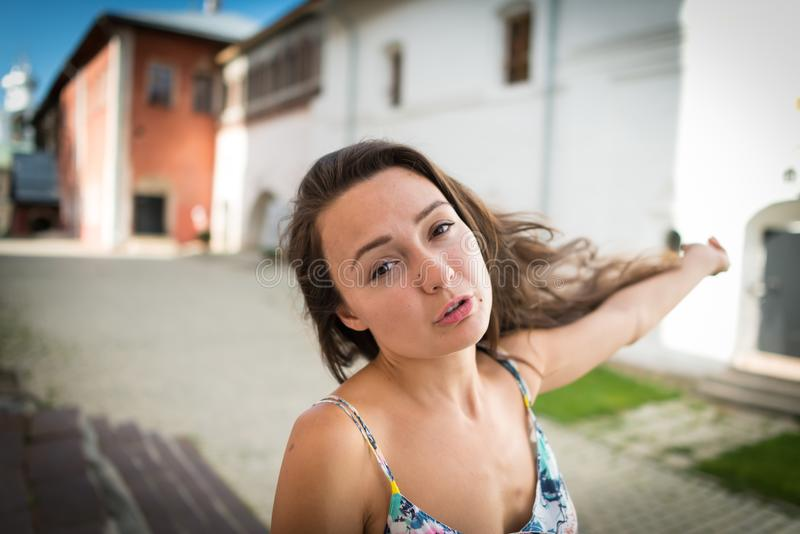Tired young woman is walking on the street in old town stock images