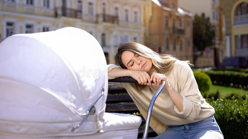 Tired young women slaapt op pasgeborene, gebrek aan energie, uitputting stock afbeelding