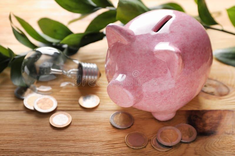 Tirelire avec des pièces de monnaie et ampoule sur le fond en bois Concept d'?nergie d'?conomie images libres de droits