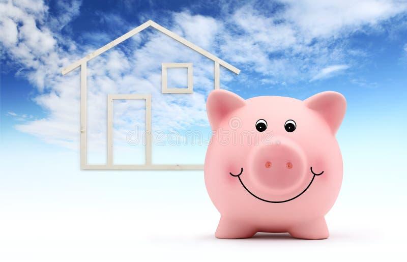 Tirelire avec la forme de maison en bois d'isolement sur le fond de ciel bleu, le bâtiment vert et les économies d'énergie photographie stock