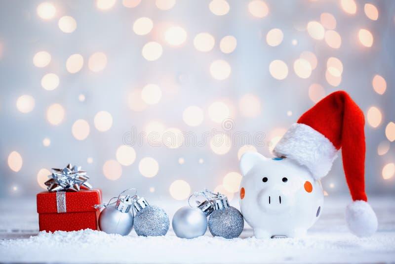 Tirelire avec le chapeau de Santa Claus sur le fond de vacances Carte de voeux de vacances image libre de droits