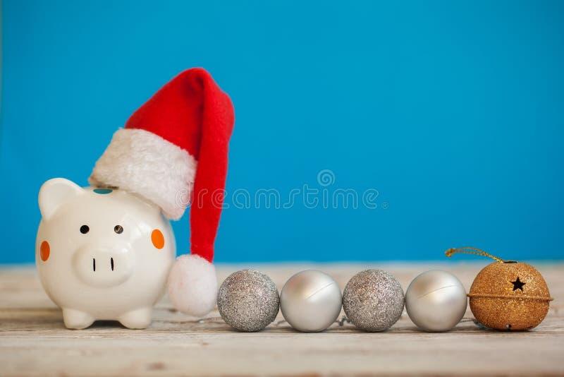 Tirelire avec le chapeau du père noël sur le fond bleu Concept de Noël et d'an neuf photographie stock libre de droits