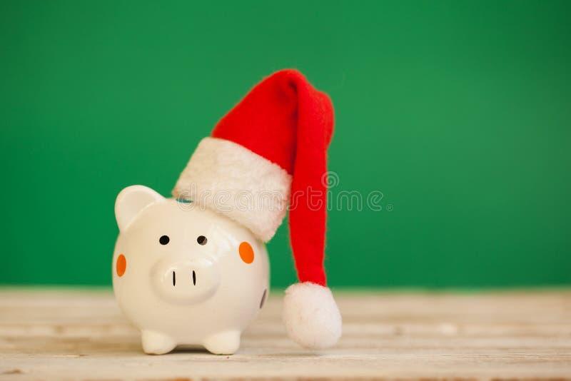 Tirelire avec le chapeau du père noël sur le fond vert Concept de Noël et d'an neuf photos stock