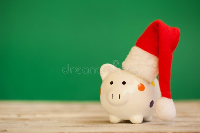 Tirelire avec le chapeau du père noël sur le fond vert Concept de Noël et d'an neuf photo stock