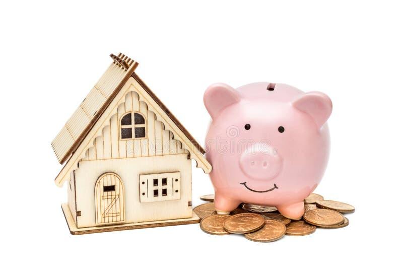Tirelire avec le modèle de la maison et le tas des pièces de monnaie sur le blanc Argent de l'?pargne pour la maison d'achat images stock