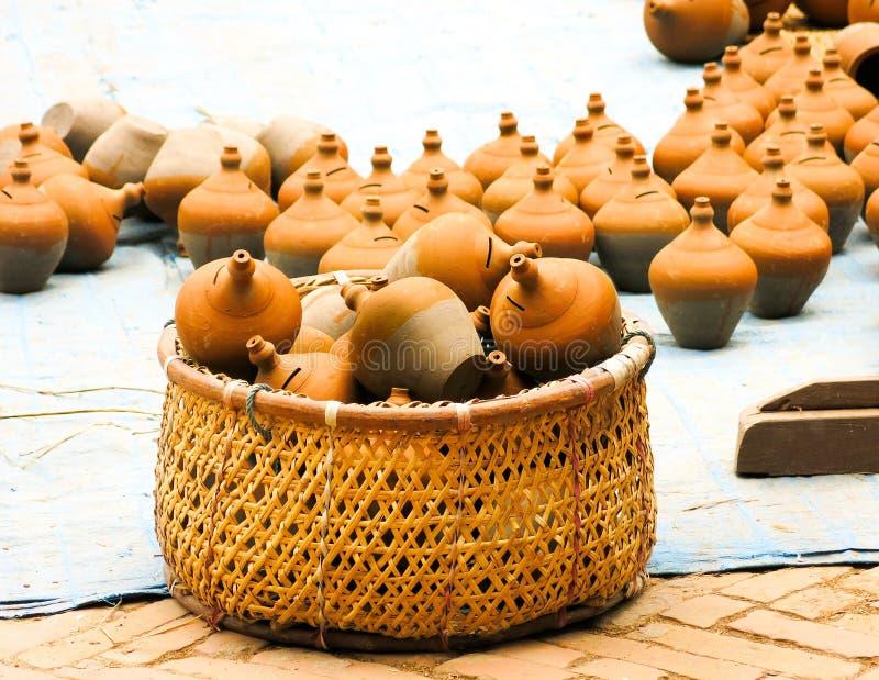 Tirelire de poterie dans le panier image stock