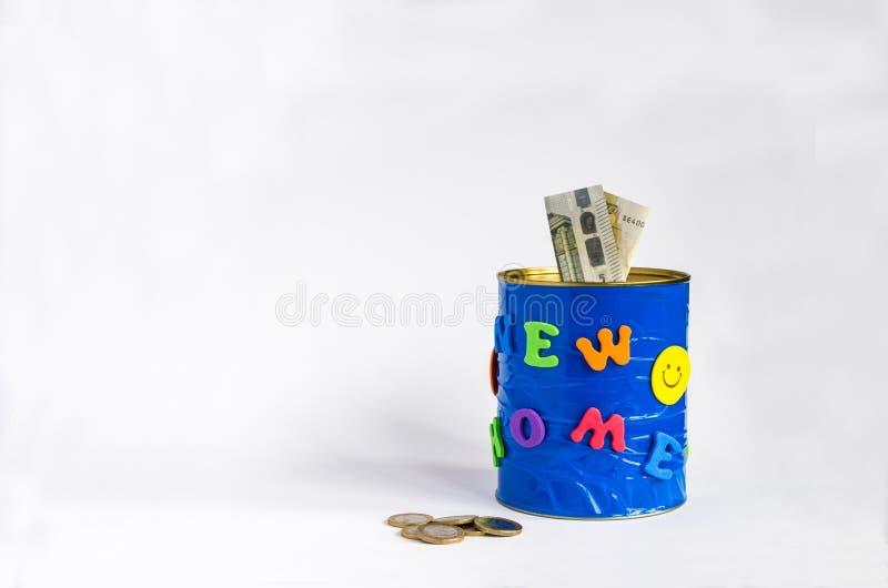 Tirelire faite main avec la nouvelle inscription à la maison, les euro billets de banque et quelques pièces de monnaie Fond blanc photos stock