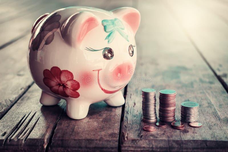 Tirelire mignonne avec la pièce de monnaie sur la vieille table en bois photo stock