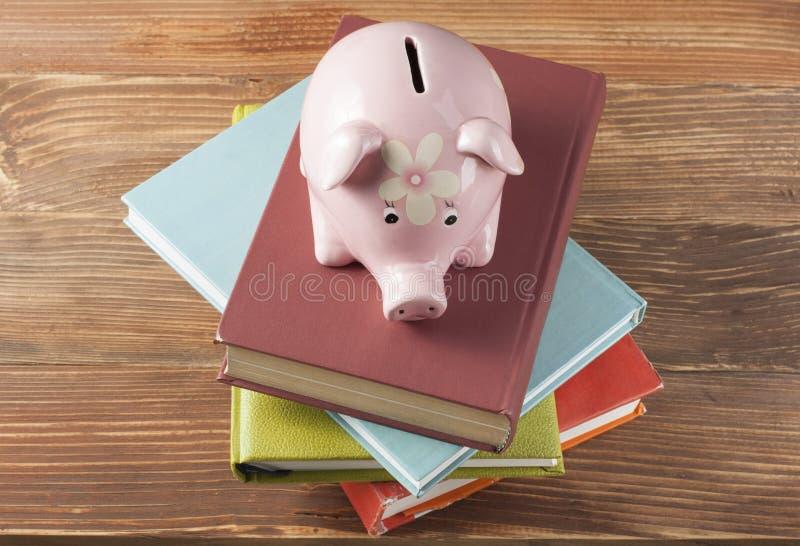 Tirelire rose avec des livres sur le fond en bois Concept d'éducation de placement image stock