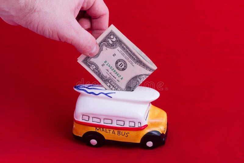 Tirelire, sous forme d'autobus en céramique avec une dénomination de deux dollars, sur un fond rouge Le concept de l'argent d'éco photos stock