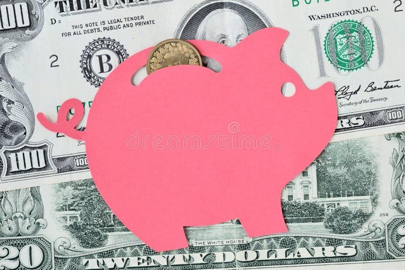Tirelire sur des billets de banque du dollar et des pièces de monnaie - concept économisant d'argent photographie stock libre de droits