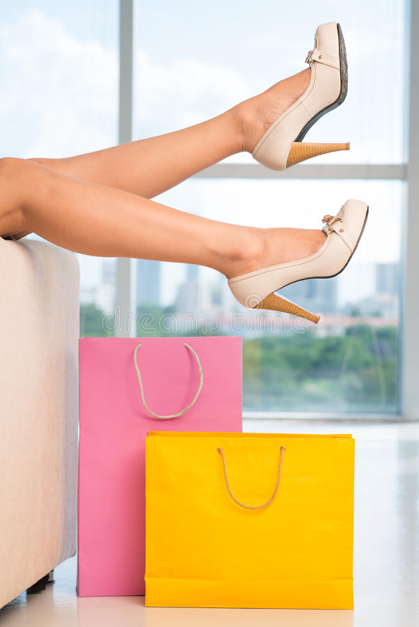 Tiresome shopping. Cropped image of a tired female shopper and shopping bags on the floor stock image