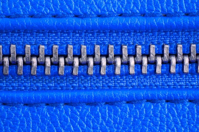 Tirette en métal sur la fin bleue intense de détail de veste en cuir ou de bourse vers le haut du macro La tirette est attache ét image stock