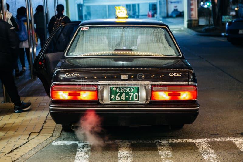 Tirez au-dessus du taxi noir de couleur avec la lumière rouge et de la fumée de la prise sur la route la nuit à Sapporo Le Hokkai photo stock