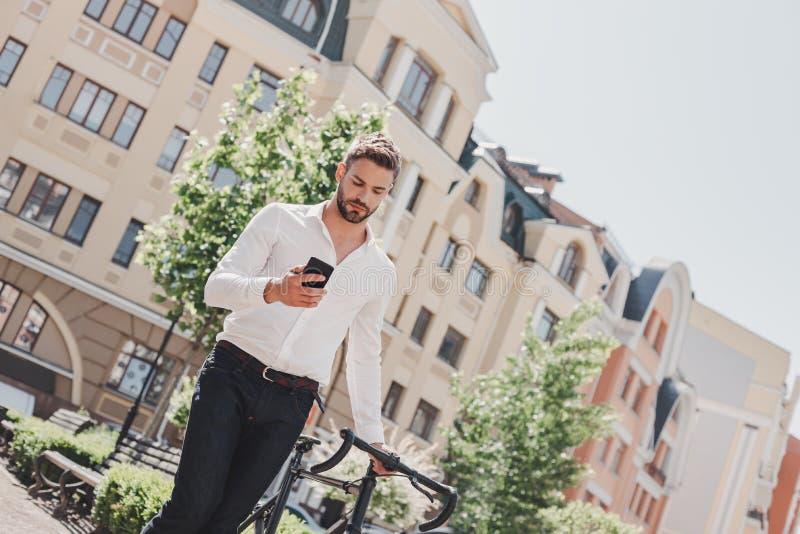 Tirez le meilleur de vous-même Jeune position châtain d'homme en parc avec une bicyclette et regarder son téléphone images stock