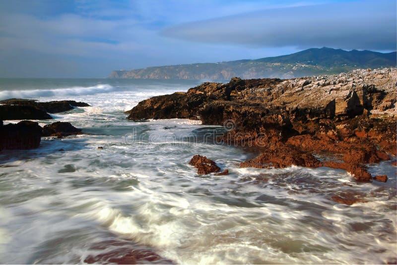 Tiri con le rocce, le onde effluiscono ed annebbiano fotografia stock