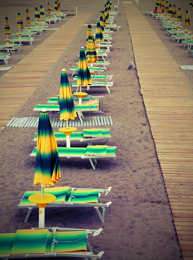 tiri con una serie di parasoli e di annata del wirh di sedie a sdraio E-F immagine stock libera da diritti