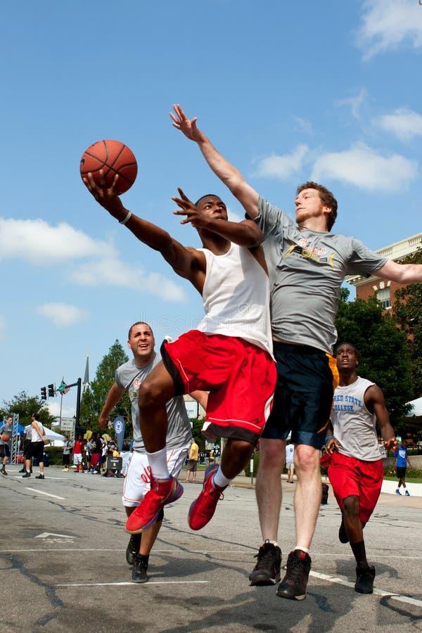 Tiri dell'uomo contro la protezione nel torneo all'aperto di pallacanestro della via fotografia stock libera da diritti