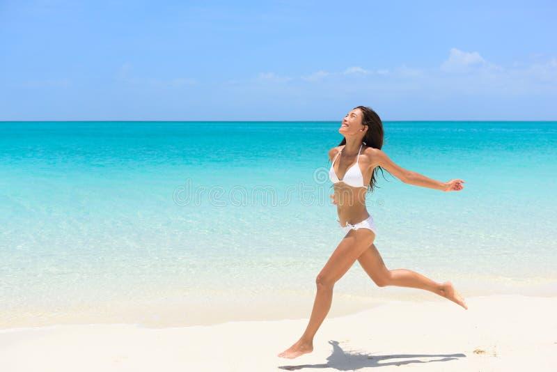 Tiri il funzionamento in secco spensierato della donna del bikini nel divertimento di libertà immagini stock