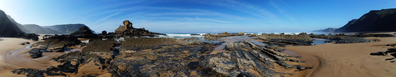 Tiri il panorama in secco con le formazioni rocciose esposte della lava a bassa marea immagini stock libere da diritti