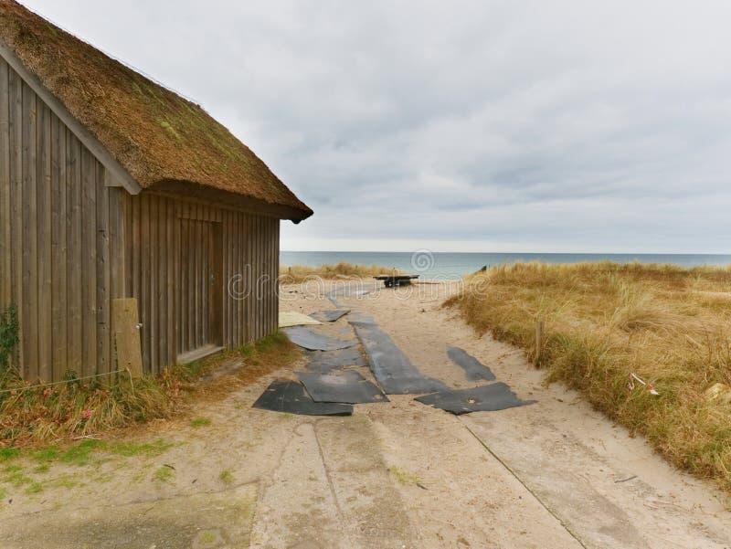 Tiri la capanna in secco alle dune di sabbia, estremità del mare seguente della strada Vecchia casa di legno per i pescatori fotografia stock