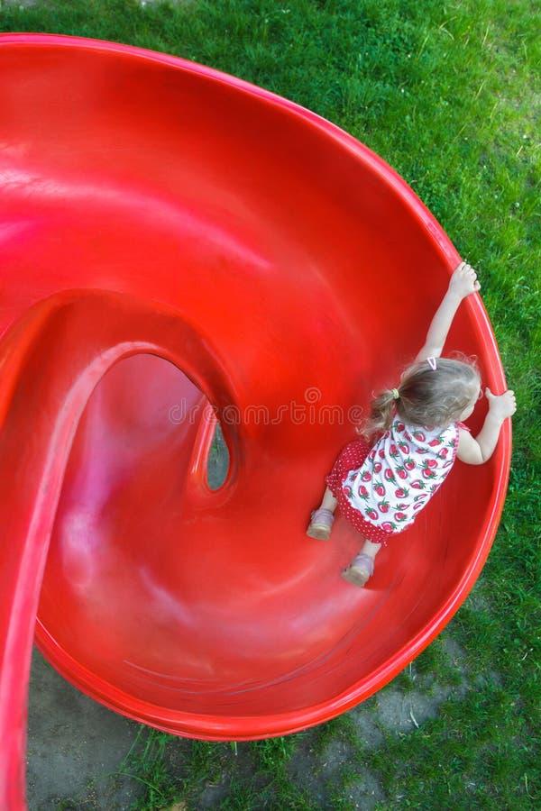 Tiro aéreo da menina loura pequena que desliza para baixo a corrediça espiral plástica vermelha do campo de jogos imagem de stock