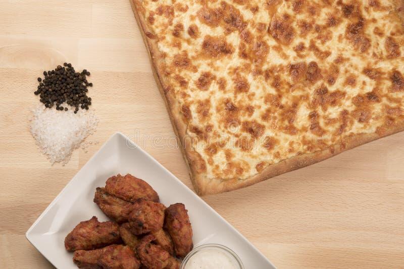 Tiro aéreo das asas de galinha em uma bacia com uma pizza de queijo quadrado-dada forma foto de stock royalty free