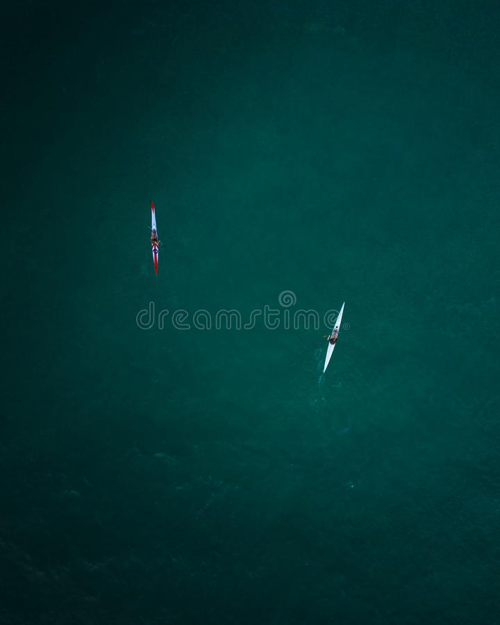 Tiro aéreo de dois caiaque que cruzam no mar aberto imagem de stock royalty free
