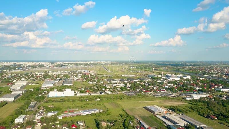 Tiro aéreo de levantamiento del aeroplano comercial que saca de un aeropuerto internacional imagen de archivo